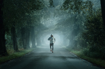 Fototapeten Fontane Man running on an empty road on the foggy morning with copy space