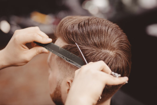 Close-up, master hairdresser does hairstyle with scissors comb. Concept Barbershop