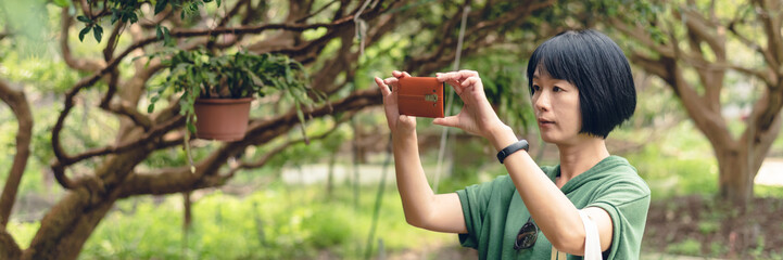 Asian mature woman take a picture at a fruit farm, banner of travel and technology concept