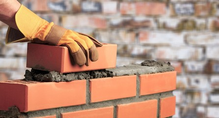 Worker builds a brick wall in the