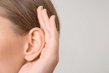 Young woman with hearing problem on light background, closeup Fototapete