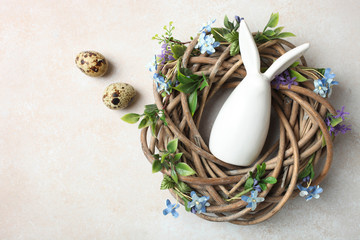 nest with quail eggs and white Easter bunny