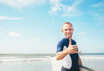 Young man Surfer portrait showing surfer's famous Shaka sign gesture in camera when he comming with long surf board to waves. Active holidays spending concept.