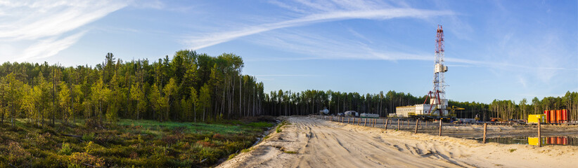 a panorama of a drilling rig on a sand dumping in the forest in the morning Fototapete