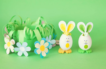 Easter holiday concept with cute handmade funny eggs bunny  in a homemade paper flower basket with a greeting text