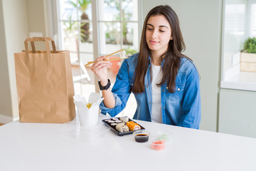 Beautiful young woman eating asian sushi from home delivery with a confident expression on smart face thinking serious