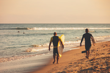 Two surfers walking down the beach with their surfboards