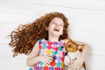 Laughing girl embracing the dog laying on a warm wooden floor.