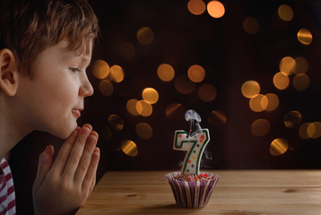 Cute little child blowing a candles on birthday cakes.