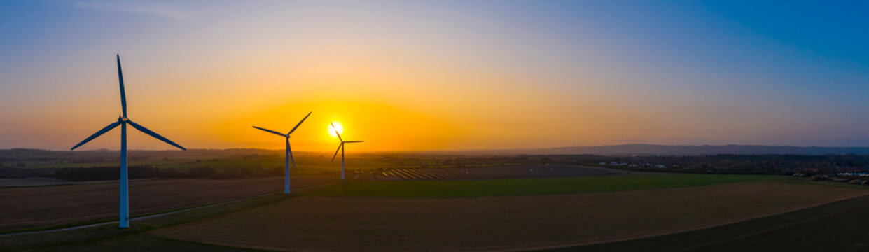 Aerial view of a wind farm during a dramatic sunrise in the English countryside, England panoramic