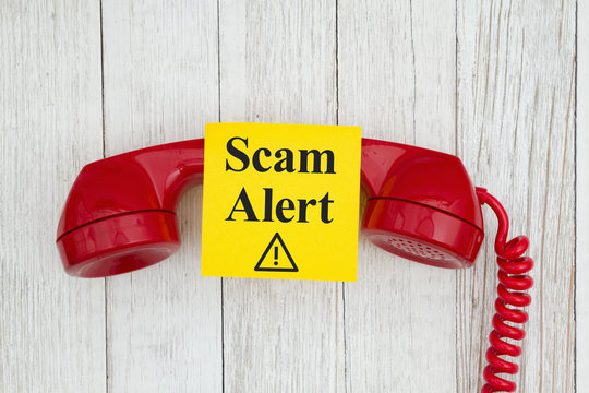 Scam alert message on sticky note on retro red phone on weathered whitewash textured wood background