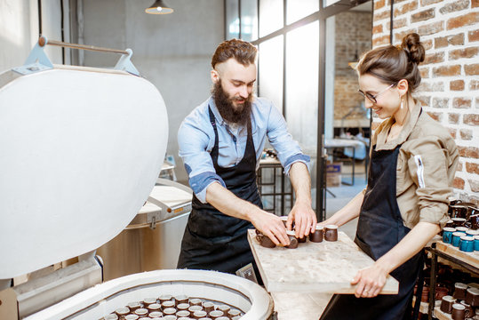 Man and woman taking baked ceramics from eleectric oven, working at the pottery manufacturing