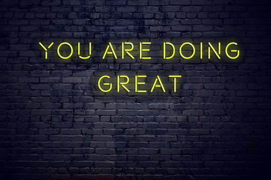 Positive inspiring quote on neon sign against brick wall you are doing great
