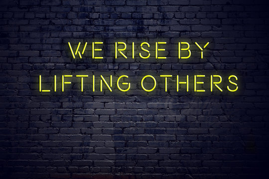 Positive inspiring quote on neon sign against brick wall we rise by lifting others