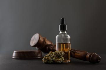 Cannabis, Cannabis Öl in Flasche und Richterhammer grauer Hintergrund