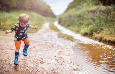 Boy with rubber boots enjoys rainy day in rural surrounding
