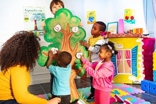 Little kids in nursery put letters on the tree