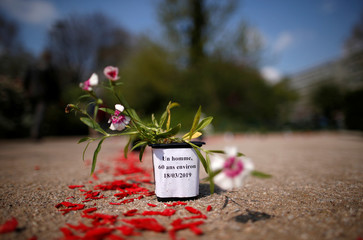 A pot of flowers in tribute to an unknown homeless man who died in a street last March 18 is seen during a ceremony in Paris