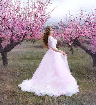 Beautiful girl in a blooming spring garden. She's wearing  a wedding dress
