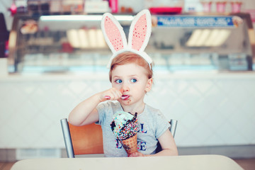 Cute funny Caucasian blonde girl child with blue eyes wearing headband with Easter bunny ears eating licking ice cream frozen food in large waffle cone with spoon. Happy childhood lifestyle
