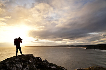 Man photographing with camera while standing on rock