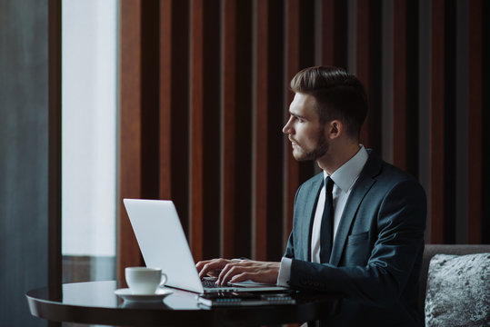 Young handsome man sitting in office with cup of coffee and working on project connected with modern cyber technologies. Businessman with notebook trying to keep deadline in digital marketing sphere.