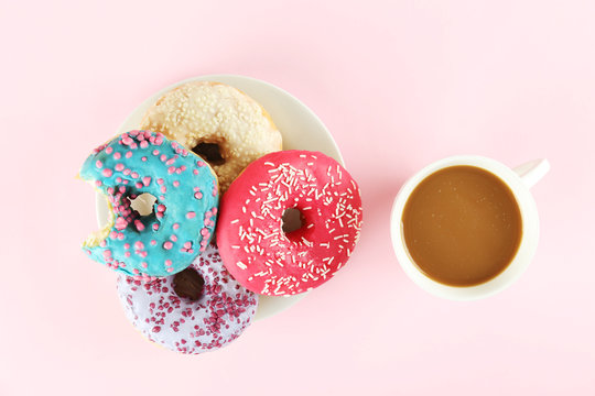 Vibrant composition of lush donut with colorful sprinkled icing, on bright background with a lot of copy space for text. Tasty but unhealthy food concept. Close up, flat lay, top view.