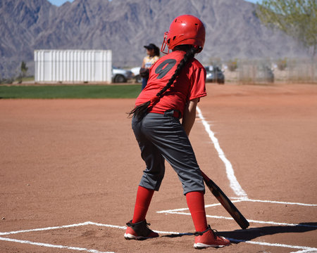 youth softball batter with long braid
