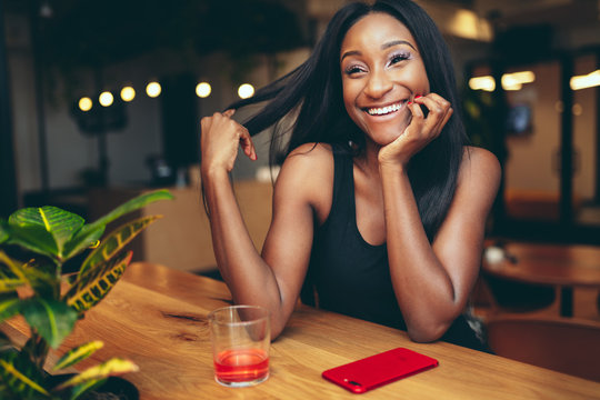 Smiling young woman sitting in restaurant