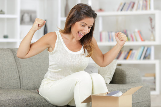 happy woman opening online order packaging surprise gift