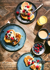 Overhead view of pancakes with fruit on wooden table