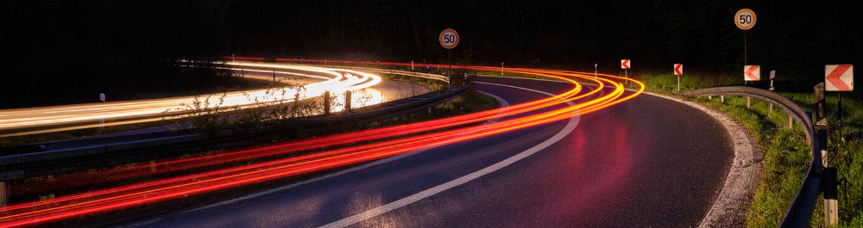 Lichtspur auf der Autobahn mit Tempo 50 Schildern in einer steilen Kurve.