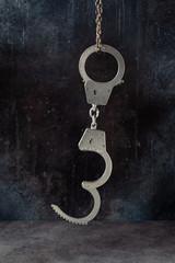 Handcuffs hanging against a grunge dark background