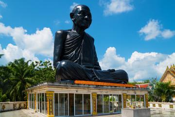 Phang Nga, Thailand, Asia- February 17, 2018, Big black sitting Buddhist Monk statue in temple Wat Kaeo Manee Si Mahathat