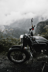 Close-up of Black motorcycle parked on the foggy road
