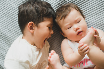 Happy brother playing with baby sister