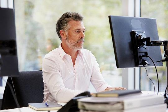 Confident Businessman Working On Computer At Desk