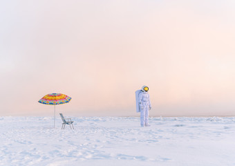 Astronaut standing at umbrella in winter