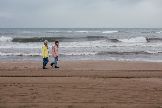 Senior woman and her daughter walking on the beach on a winter day.