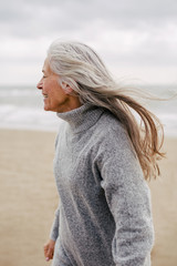 Active senior woman enjoying on the beach in winter.