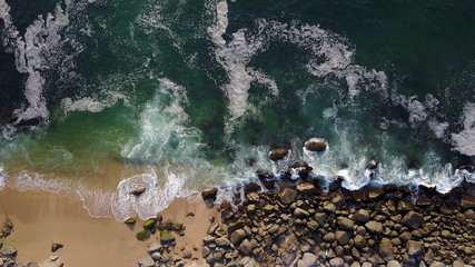 Sea wave crashing on the beach - view from drone