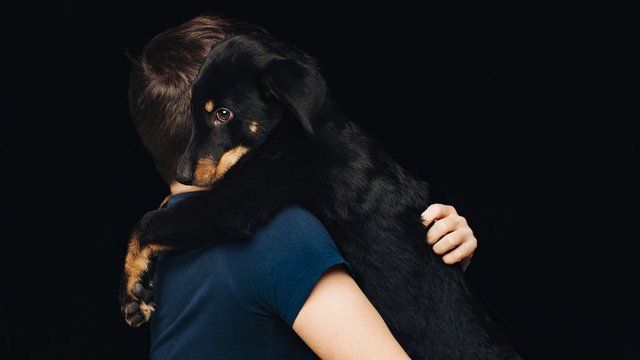 Studio shot of young man holding puppy