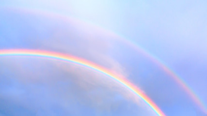 Double rainbow in the blue sky on a summer day