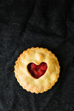 Heart topped strawberry pie on black