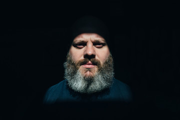 Bearded man over black background looking at camera