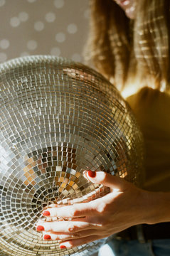 Close up view of disco ball held by woman