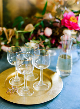 Four wine glasses on gold tray