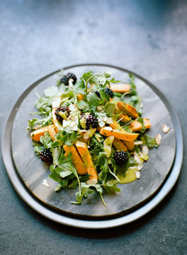 Beautifully plated blackberry and carrot salad on dark slate background