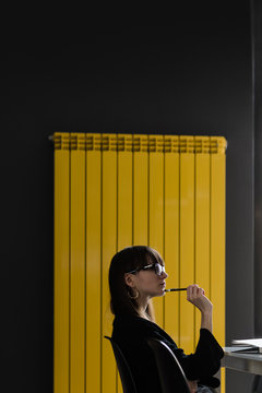 Yellow radiator portrait of a young fashionable woman