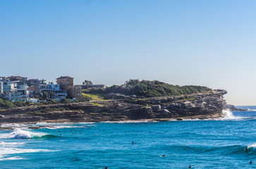 Wall Murals Northern Europe Sydney, Australia - February 11, 2019: Wider shot of Gray with green vegetation on top North Cliff point of Bronte Beach, blue sea water with swimmers, under light blue sky, seen from South cliff.